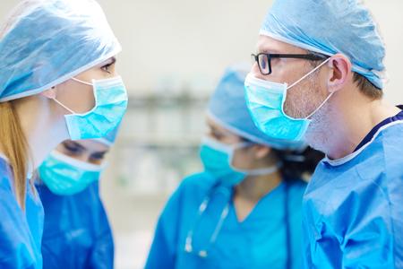 enfermera con cofia: Dos cirujanos de pie frente a frente