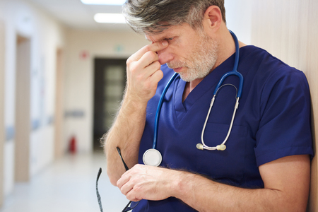 Mature doctor tired after long day Stock Photo