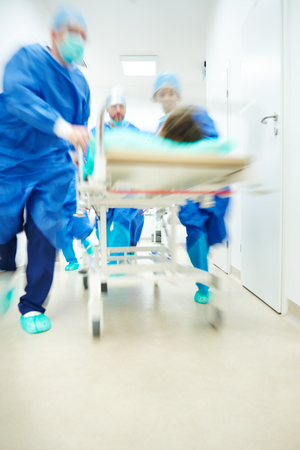 Doctors running to the operating room Stock Photo