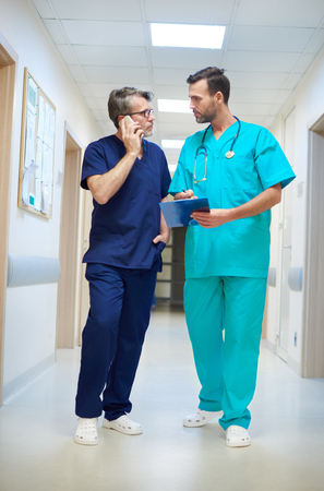 busy person: Two busy doctors on the corridor