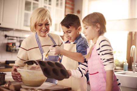 Kids and grandma making muffins  Фото со стока
