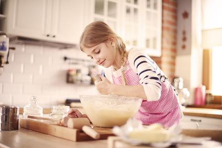 Little girl learning how to make proper dough Фото со стока