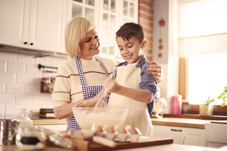 Waist up of boy and grandmother in the kitchen
