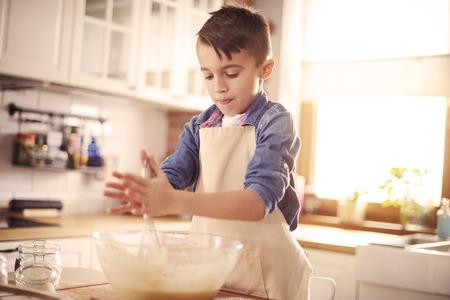 Little masterchef combine all the ingredients Фото со стока