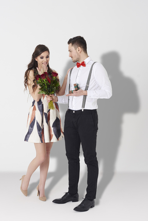 embarrassment: Side view of young man giving young woman bouquet of roses