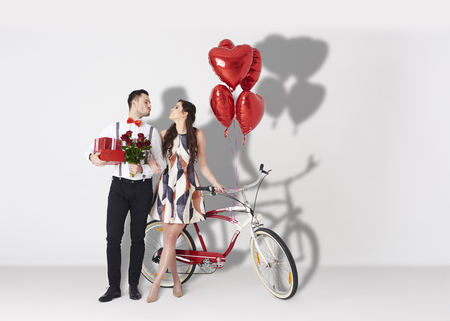 Cheerful couple with valentines accessories