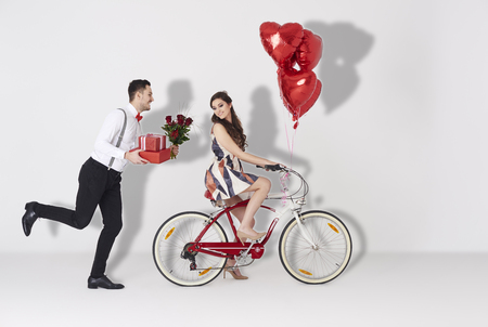 Happy couple with gift and heart shaped balloon Фото со стока