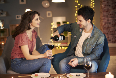 Boyfriend serving red wine while date   Stock Photo