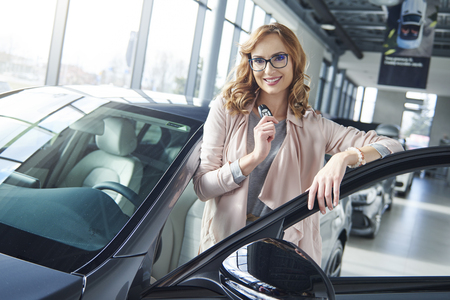 Portrait of woman with her brand new car Stock Photo