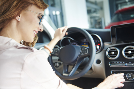 Rear view of blond woman hair testing brand new car