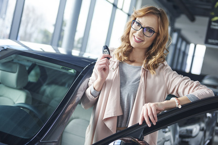 Confident woman prepared for driving by new car