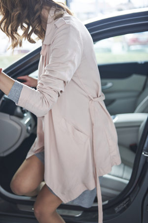 Woman getting in to her new bought car Stock Photo