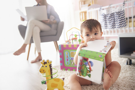 teething: Toddler playing with toys in the room Stock Photo
