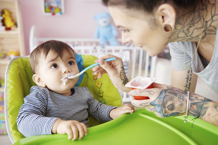 Mummy feeding boy with yoghurt Stock Photo