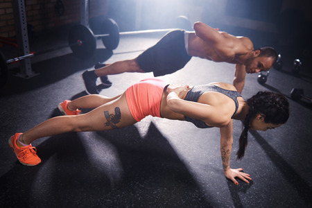push people: Two young people doing push ups together Stock Photo