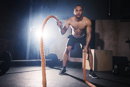 Motivated man throwing ropes at healthy club Stock Photo