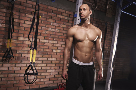 Waist up of muscular man against gym wall