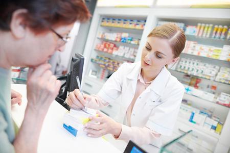 Young pharmacist helping elderly customer 版權商用圖片