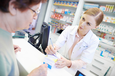 Pharmacist talking to customer about prescription Stock Photo