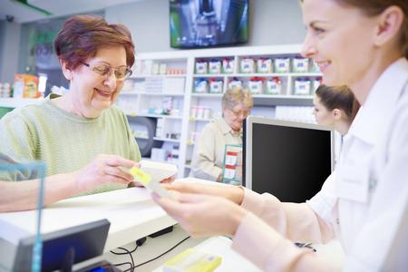 Jonge apotheker die dosis verklaart aan vrouwelijke oudste Stockfoto