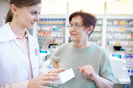 only adult: Female pharmacist assisting senior woman