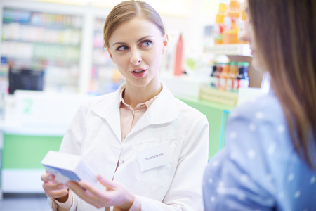 Pharmacist helping client with prescription Stock Photo