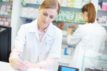 Close up of two busy female pharmacists