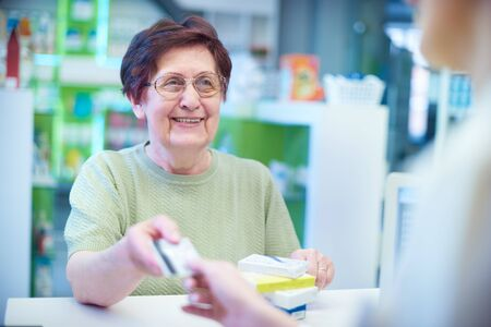 Mature woman paying for prescription