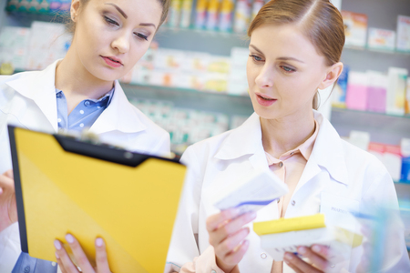busy person: Two young pharmacists doing paperwork