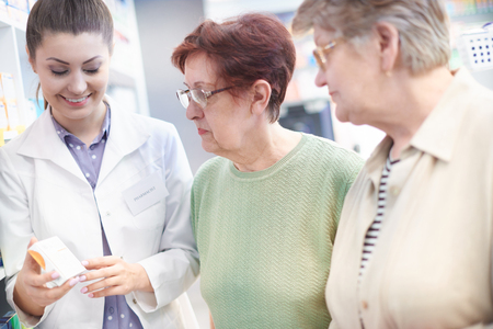 aging: Pharmacists with mature clients in drug store Stock Photo
