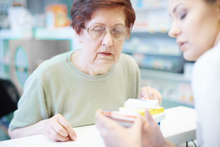Senior woman with pharmacist at checkout desk Stock Photo