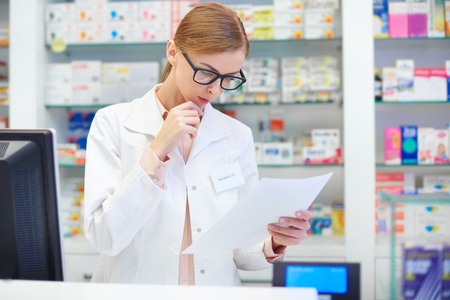 Female pharmacist checking documents at drugstore Stock Photo