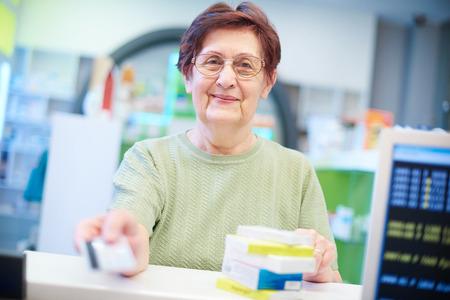 Smiling senior client in pharmacy