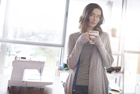 Craftswoman drinking coffee at her workshop Stock Photo
