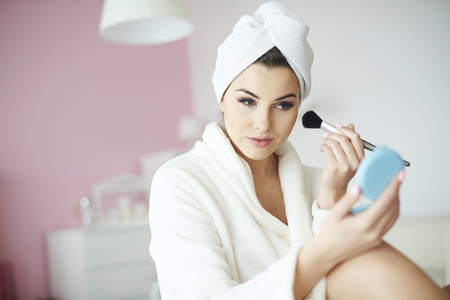 adding: Young beauty adding blusher to her cheeks
