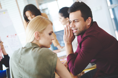 workmate: Male coworker whispering to workmate on meeting