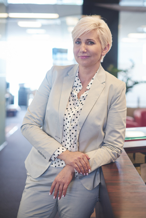 Portrait of blond senior woman in office Stock Photo