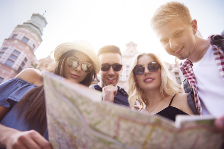 Low angle view of tourists with paper map Stock Photo