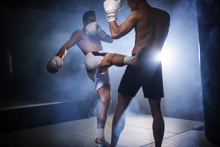 Two boxers training kicks in the gym Imagens
