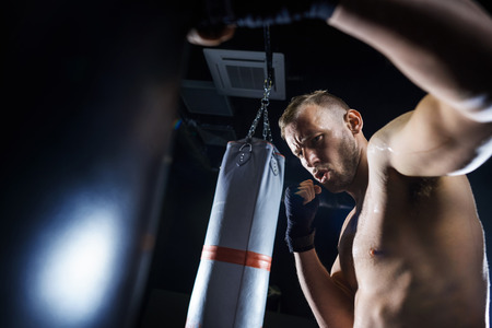 Male boxer fighting in the gym studio Stock Photo