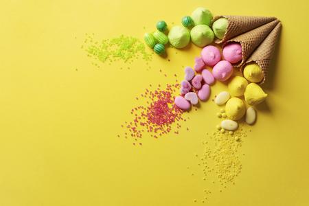 黄色の背景にさまざまなキャンディー 写真素材