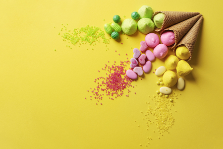 Various candies on the yellow background
