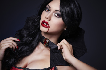 Dark hair vampire with blood on face Фото со стока - 80077417