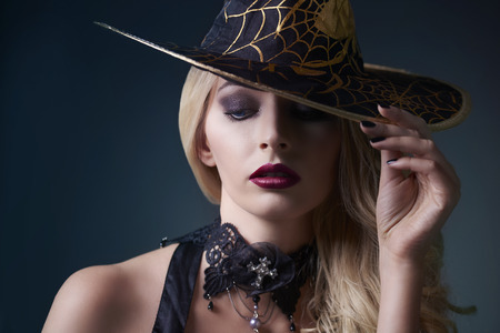 Sexy witch posing with hat