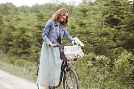 Gelukkige vrouw met fiets in het park