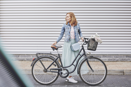 Fashionable woman with urban bike in the city