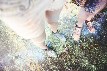 Close up of human legs dirty from festivals colors Stock Photo
