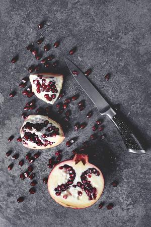 Granada de corte con cuchillo sobre la mesa Foto de archivo - 81594249