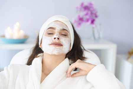 Relaxed woman is getting a face mask in spa