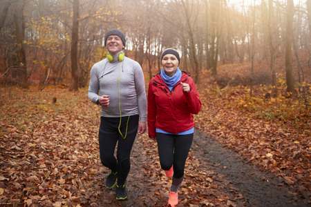 Senior couple jogging among forest path Stock Photo